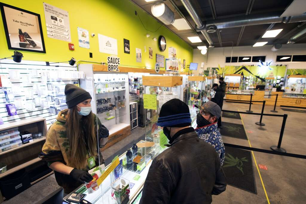 Alex Howe, left, a budtender at Altitude Organic Cannabis in Dillon, stands behind a protective plexiglass barrier while talking with customers Tuesday, Feb. 16. | Photo by Jason Connolly / Jason Connolly Photography