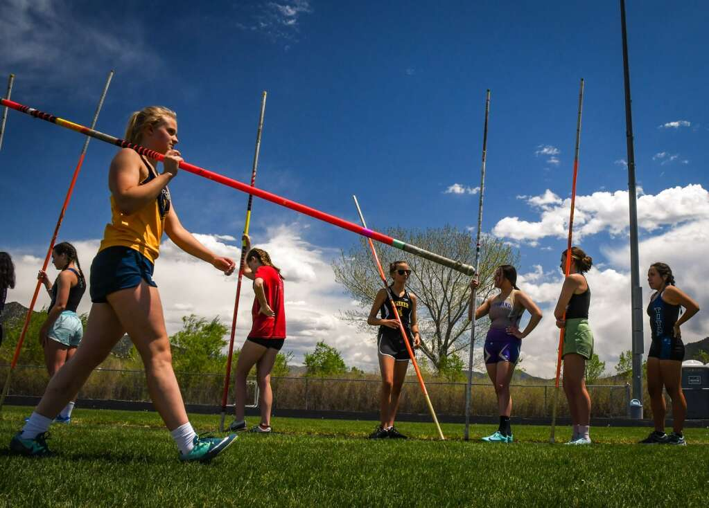 A Rifle High School pole vaulter walks back to the end of the line during warm ups for the girls pole vaulting competition.  |Chelsea Self / Post Independent