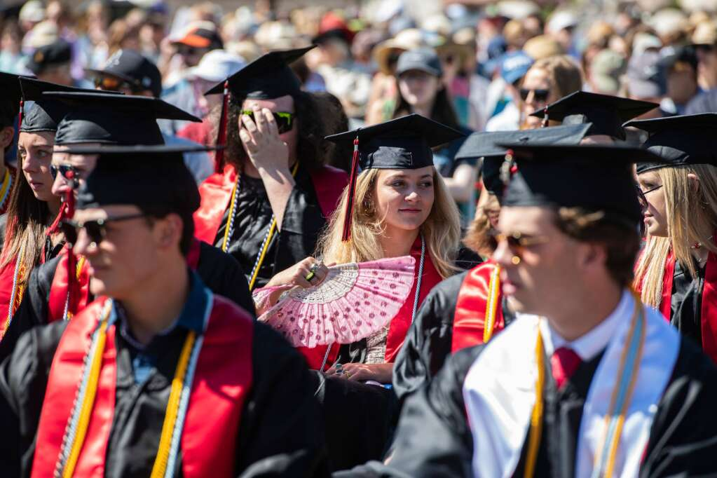 An Aspen High School graduate fans herself in the heat during the commencement ceremony on Saturday, June 5, 2021. (Kelsey Brunner/The Aspen Times)