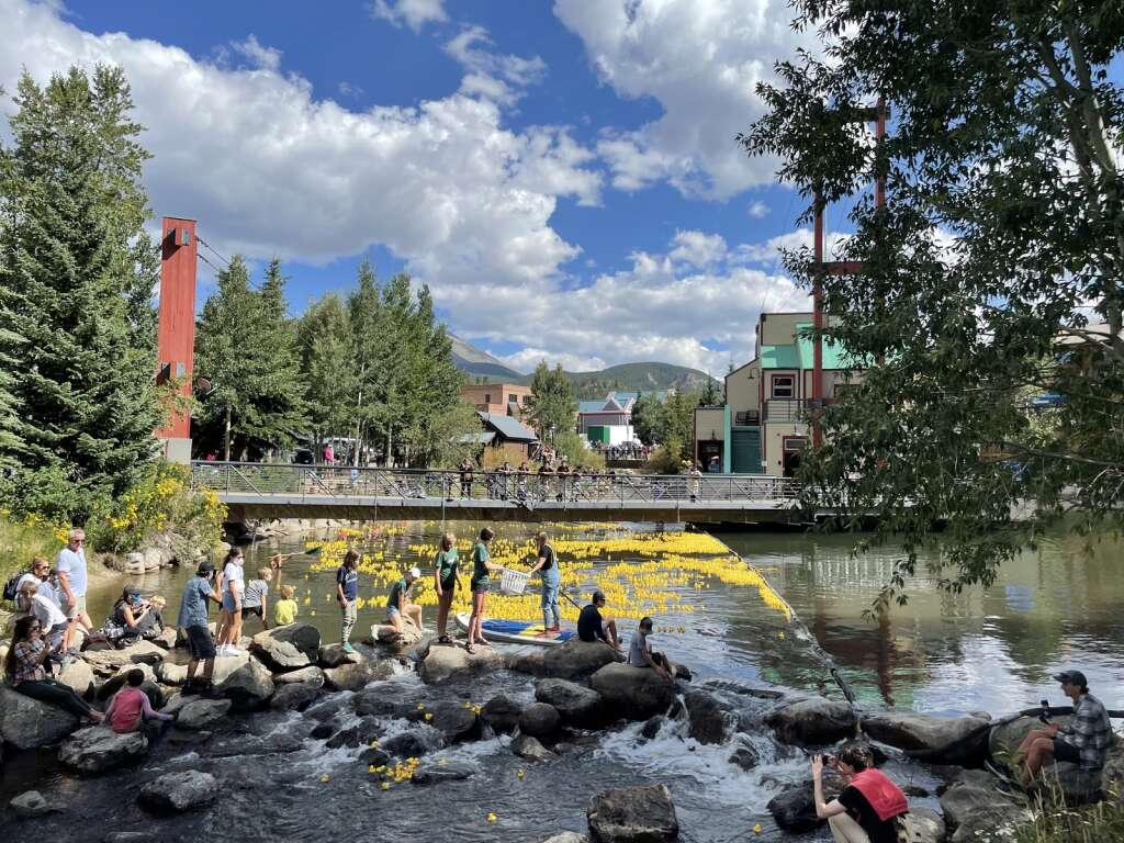 Spectators watch thousands of rubber ducks float down the Blue River at Breckenridge on Saturday September 4th.  The ducks are part of the Great Rubber Duck Race organized by the Summit Foundation.  |  Jenna deJong / Summit Daily News