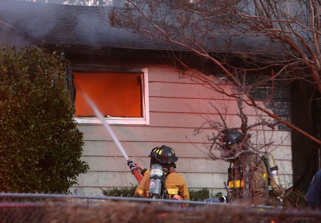 Firefighters put water into a window on a face of the multi-structure incident on Parkview Drive in Grass Valley Friday evening.