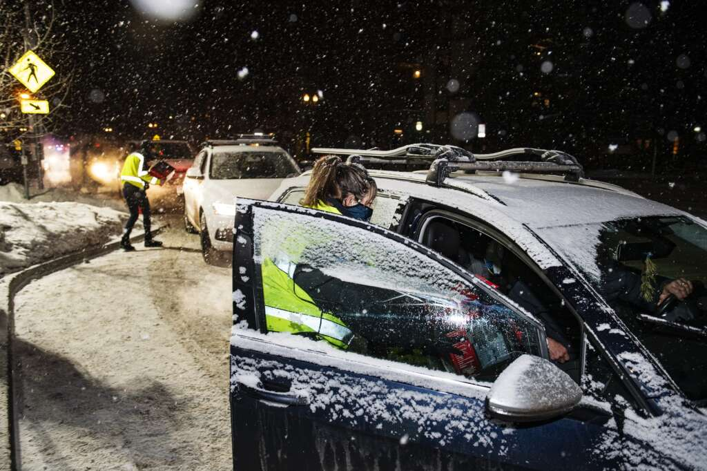 Detective Danielle Madril passes a heater into a vehicle outside of the Aspen Police Department on Monday, Dec. 28, 2020. (Kelsey Brunner/The Aspen Times)