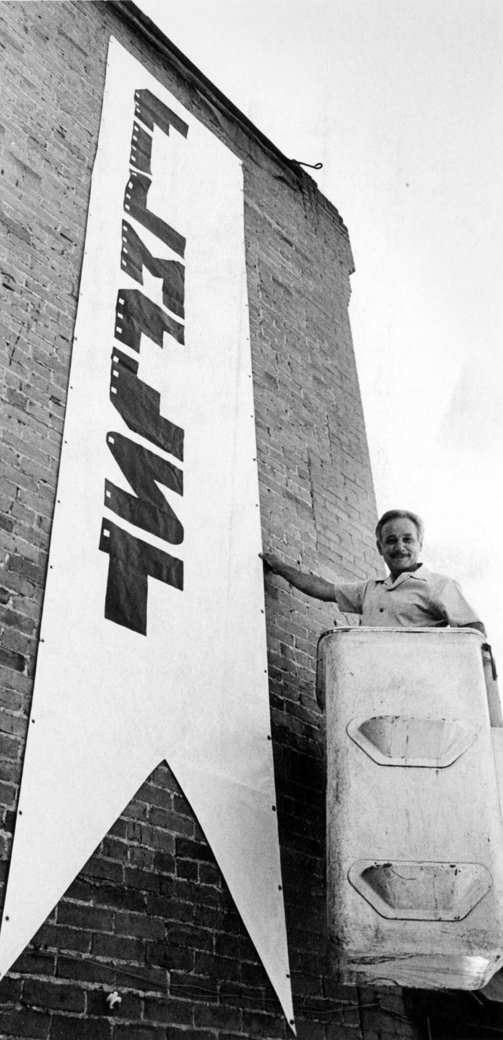 One b/w photograph of Dominic Linza, owner/manager of the Isis Theater, on a ladder putting out the banner for the Filmfest.  This image is in the Aspen Times on October 2, 1980, p. 15-B. (Aspen Historical Society, Aspen Times Collection)