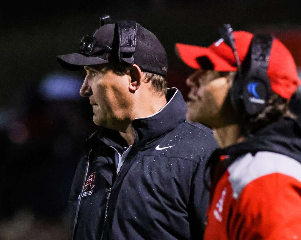 Aspen High School football coach Travis Benson, left, watches a play against Delta on Friday, Oct. 8, 2021, on the AHS turf. Photo by Austin Colbert/The Aspen Times.
