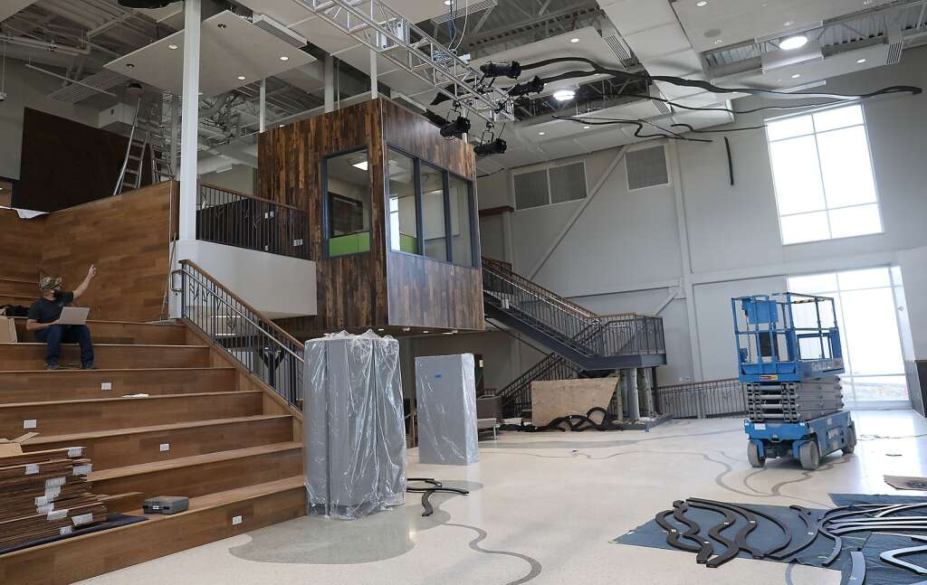 A worker at the new Sleeping Giant School works on the lighting in large common area where student performances will be held and lunch will be served.