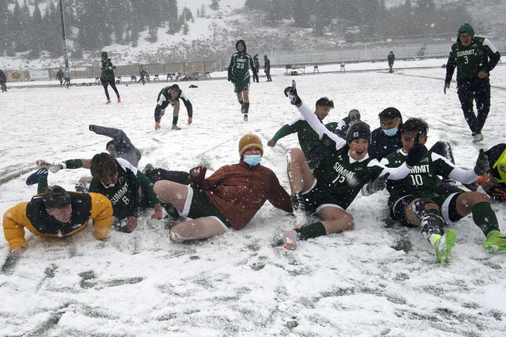 The Summit High School Tigers boys varsity soccer team slides in the snow to celebrate their 4-0 home senior night victory against the Glenwood Springs Demons on April 15, 2021 at Climax Molybdenum Field at Tiger Stadium in Breckenridge. | Photo by Jason Connolly / Jason Connolly Photography
