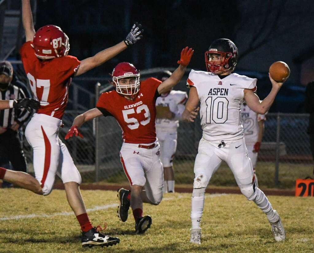 Glenwood Springs Demons Zach Cecil-Hoerl and Ian Cecil-Hoerl rush the Aspen Skier quarterback during Friday night's season opener at Glenwood Springs High School. |Chelsea Self / Post Independent