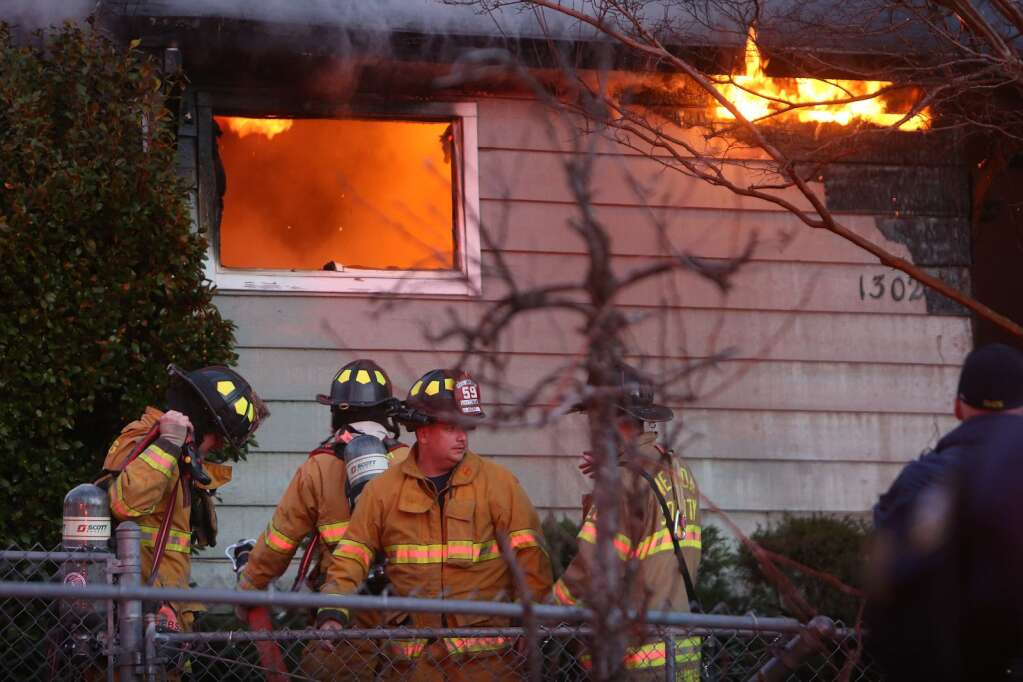 Firefighters don breathing apparatusÕ before entering the structure fire Friday evening off of Parkview Drive in Grass Valley.
