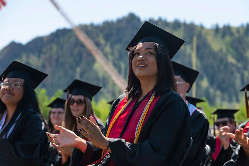 An Aspen High School graduate claps for the speaker during the commencement ceremony on the turf field on Saturday, June 5, 2021. (Kelsey Brunner/The Aspen Times)