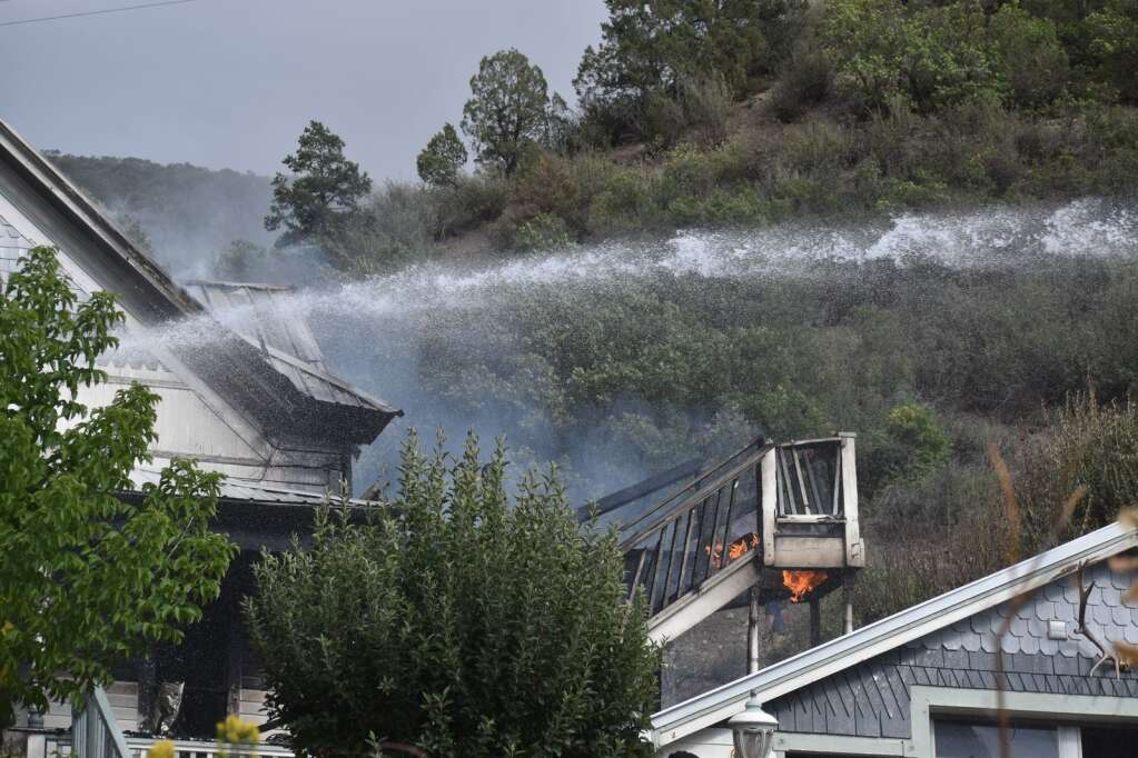 Water sprays toward a burning house in Glenwood Springs on Saturday. |Ray K. Erku / Post Independent