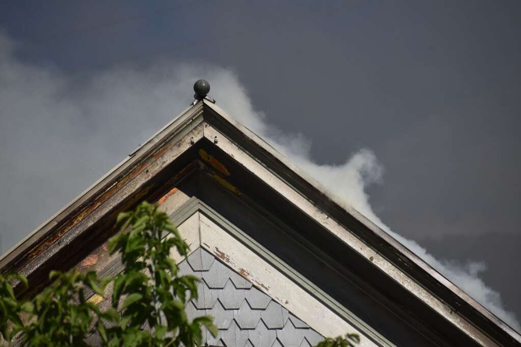 Smoke rises off the roof of a burning house in Glenwood Springs on Saturday. |Ray K. Erku / Post Independent