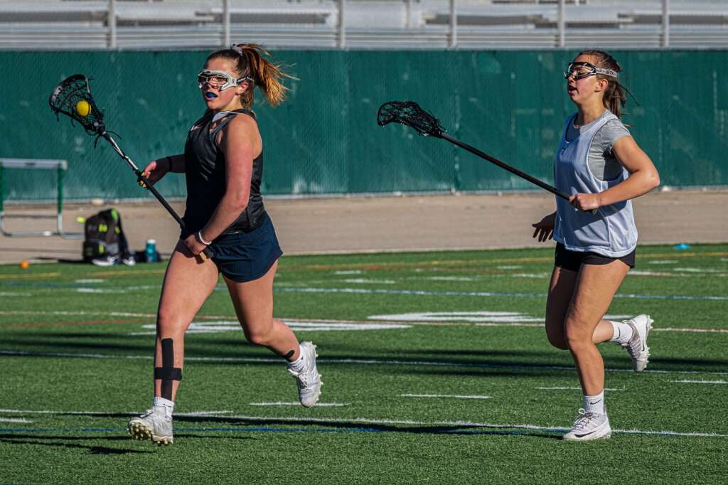 Lindsay Davis and Chloe Nicholds run downfield at Summit High School varsity girls lacrosse practice at Tiger Stadium in Breckenridge on Thursday, May 7, 2021. | Photo by Joel Wexler / Rocky Mountain.Photography