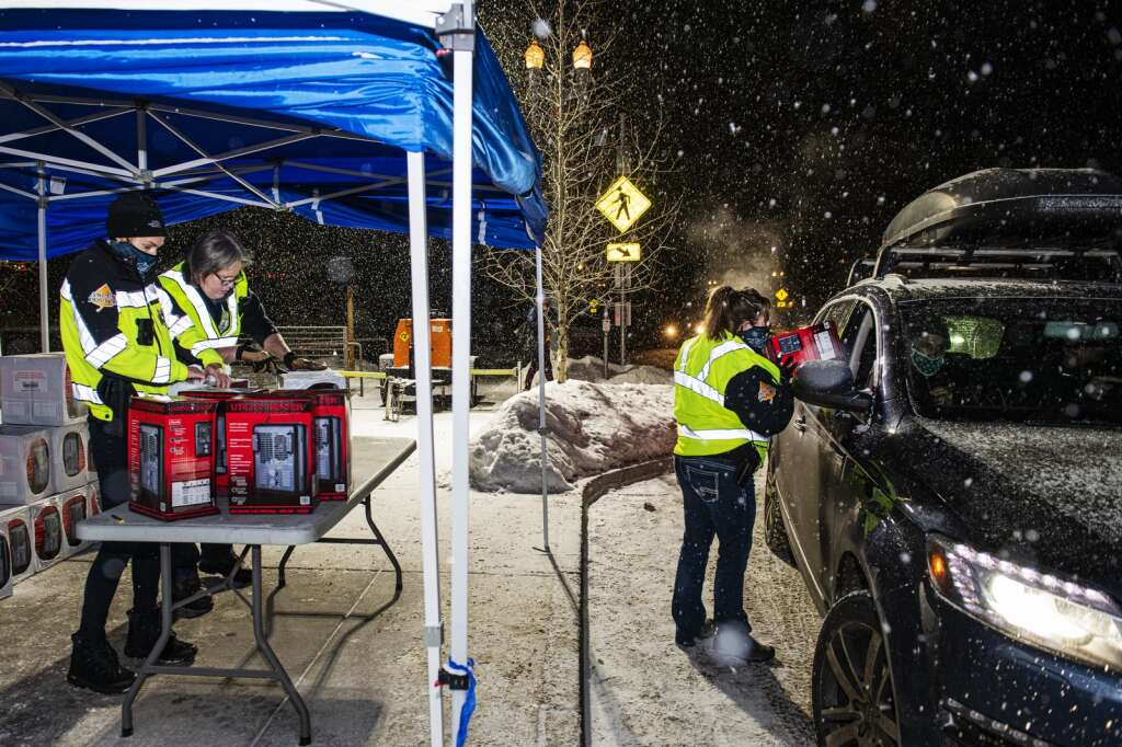 Detective Danielle Madril passes a heater into a vehicle while community response officer Rachel Beck, left, and Sgt. Terry Leitch unwrap boxes of heaters outside of the Aspen Police Department on Monday, Dec. 28, 2020. (Kelsey Brunner/The Aspen Times)