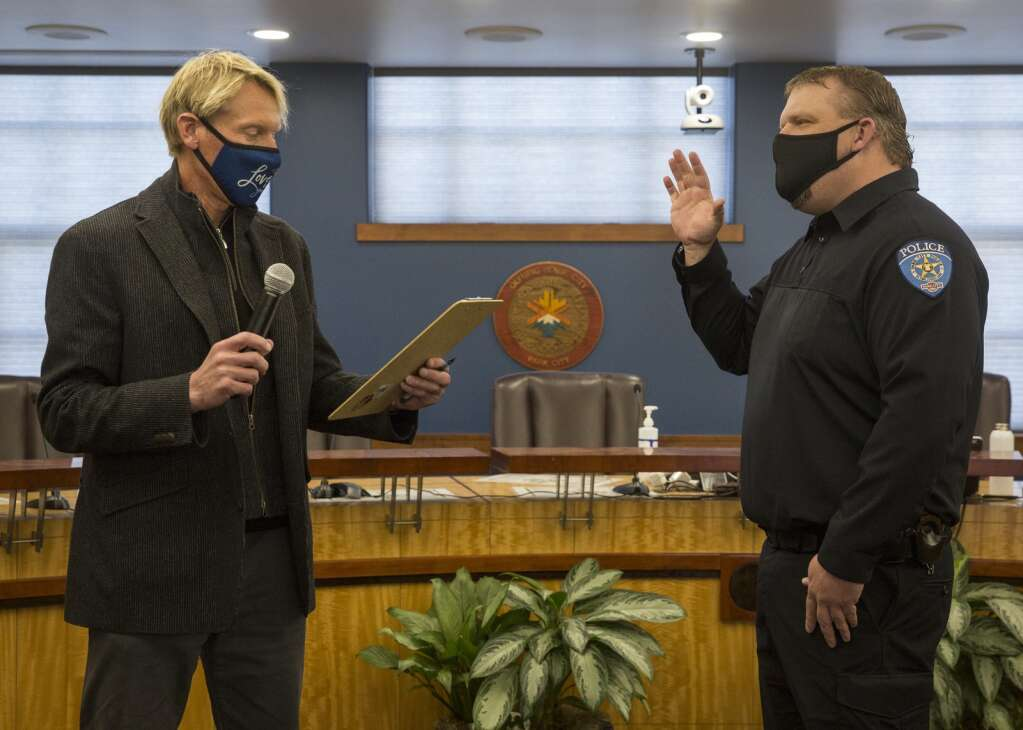 Mayor Andy Beerman, left, reads from a clipboard as he swears-in Park City Police Officer Brandon Smalling during the council meeting Thursday, April 1, 2021, at City Hall. (Tanzi Propst/Park Record)