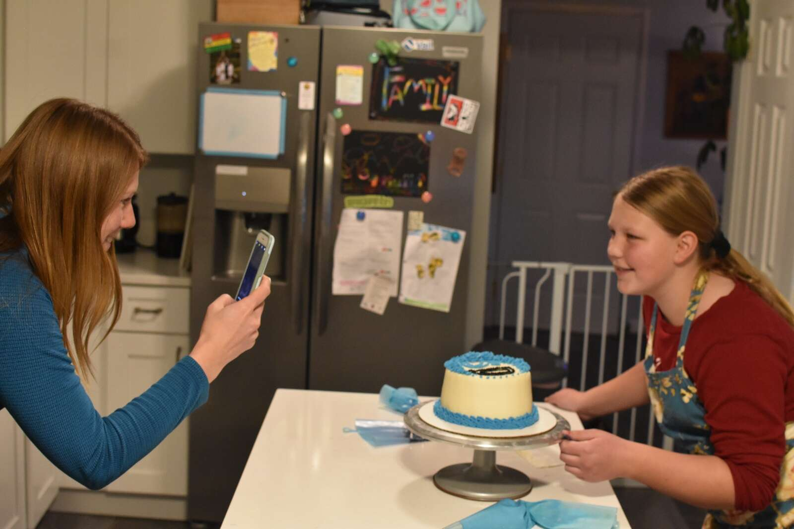 Andrea Beacham, left, photographs her daughter River Close with her most recent completed cake design on Wednesday, Dec. 2. | Photo by Steven Josephson / sjosephson@summitdaily.com