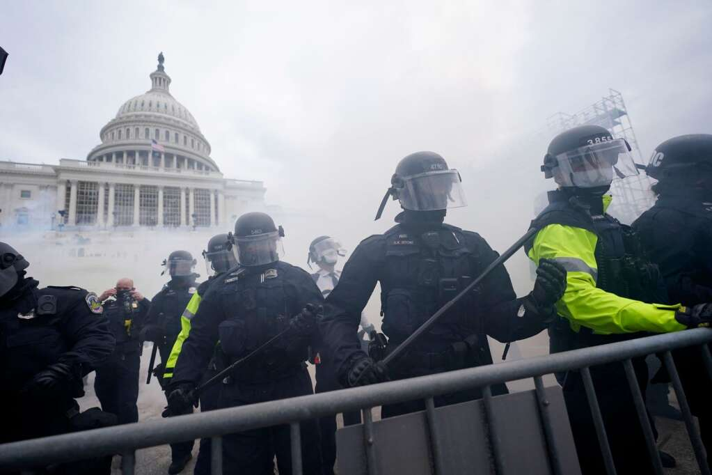 Police stand guard after holding off Trump supporters who tried to break through a police barrier, Wednesday, Jan. 6, 2021, at the Capitol in Washington. As Congress prepares to affirm President-elect Joe Biden's victory, thousands of people have gathered to show their support for President Donald Trump and his claims of election fraud.  (AP Photo/Julio Cortez)