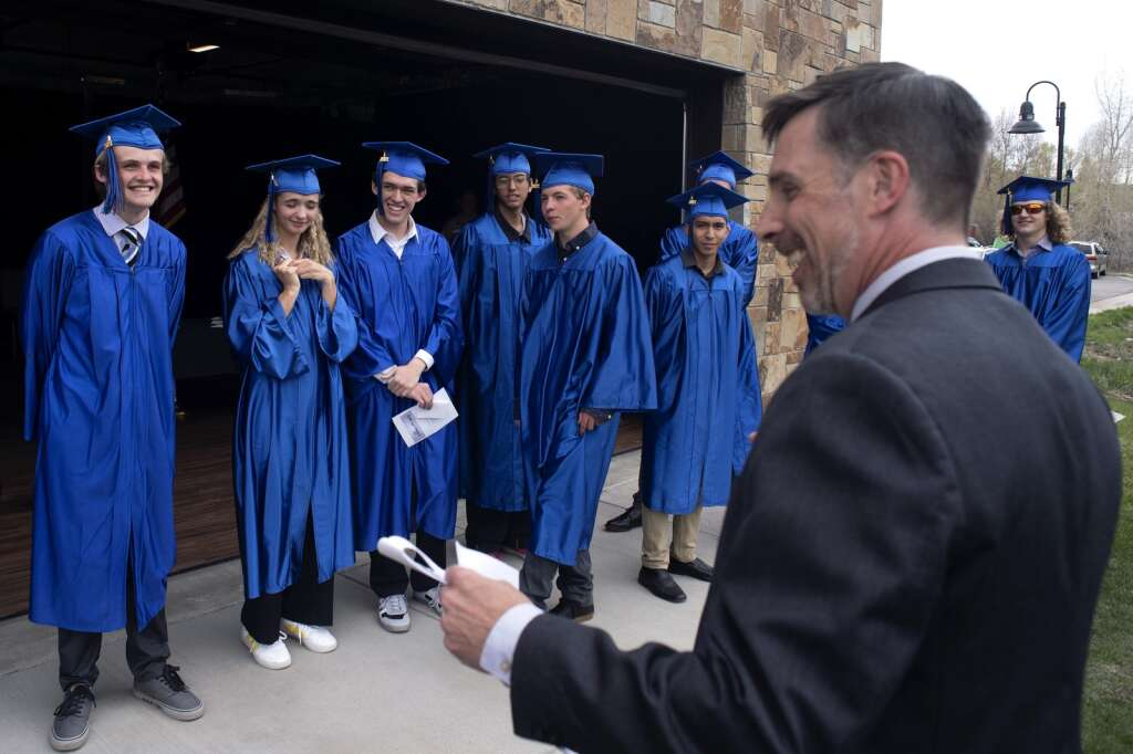 Snowy Peaks High School seniors share a laugh with Principal James Smith prior to graduation Wednesday, May 26, at the Silverthorne Performing Arts Center in Silverthorne.   Photo by Jason Connolly / Jason Connolly Photography