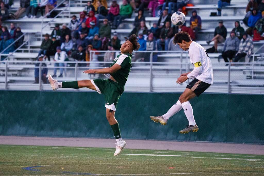 Summit sophomore Santiago Casco heads the ball away from a leaping defender during the Summit Tigers homecoming match against Battle Mountain on Tuesday, Sept. 21, at Tiger Stadium in Breckenridge. | John Hanson/For the Summit Daily News