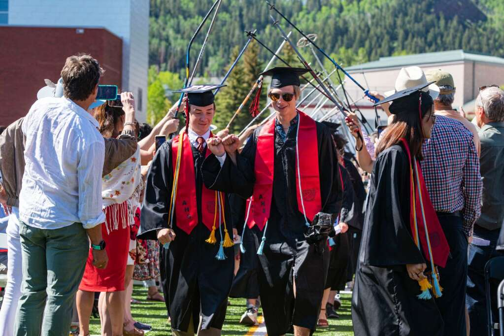 Aspen High School graduates process into the stadium under ski poles held by parents and teachers for their 2021 commencement ceremony at the football stadium on Saturday, June 5, 2021. (Kelsey Brunner/The Aspen Times)