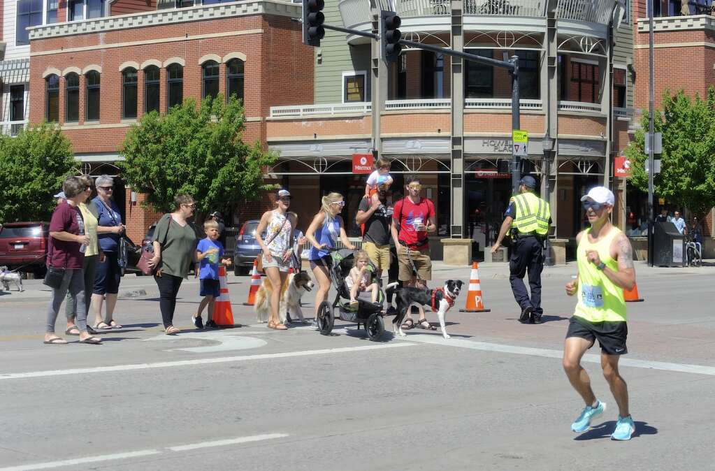 An officer halts pedestrians in the middle of a cross walk on Lincoln Ave. as Nolan Johnson runs the last stretch of the Steamboat Marathon on Sunday morning. (Shelby Reardon)