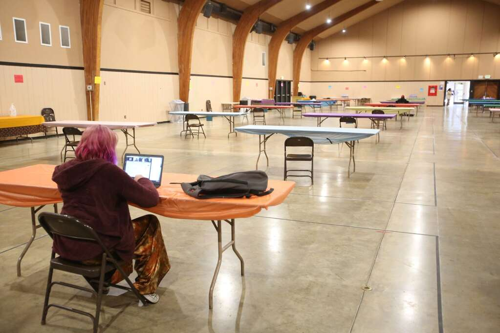 Student Ella Lock works on her science work Wednesday from the new student work space set up inside of the main building at the Nevada County Fairgrounds. | Photo: Elias Funez