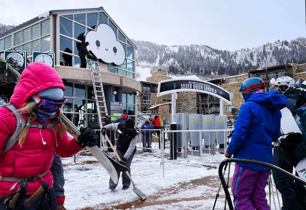 """Aspen Snowmass employees install a large """"Little Cloud"""" piece from collaborative artist duo FriendsWithYou on the top of the Silver Queen Gondola building at the base of Aspen Mountain on Wednesday, Dec. 23, 2020. The collaborative work from Samuel Borkson and Arturo Sandoval III decorate the 2020-21 lift passes. (Kelsey Brunner/The Aspen Times)"""