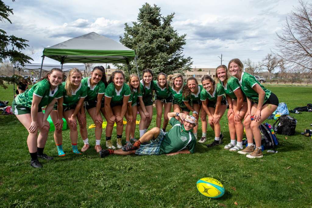 Coach Karl Barth and the Summit High girls rugby team celebrate with a team photo after winning their final game against Monarch at the high school rugby state championships on Saturday, May 1, 2021, at Cook Park in Denver, Colo. As the Tigers won their first game, tied the second, and claimed victory in the third, the Summit High girls rugby team clinched their 13th-straight state championship title. | Photo by Liz Copan  /Studio Copan