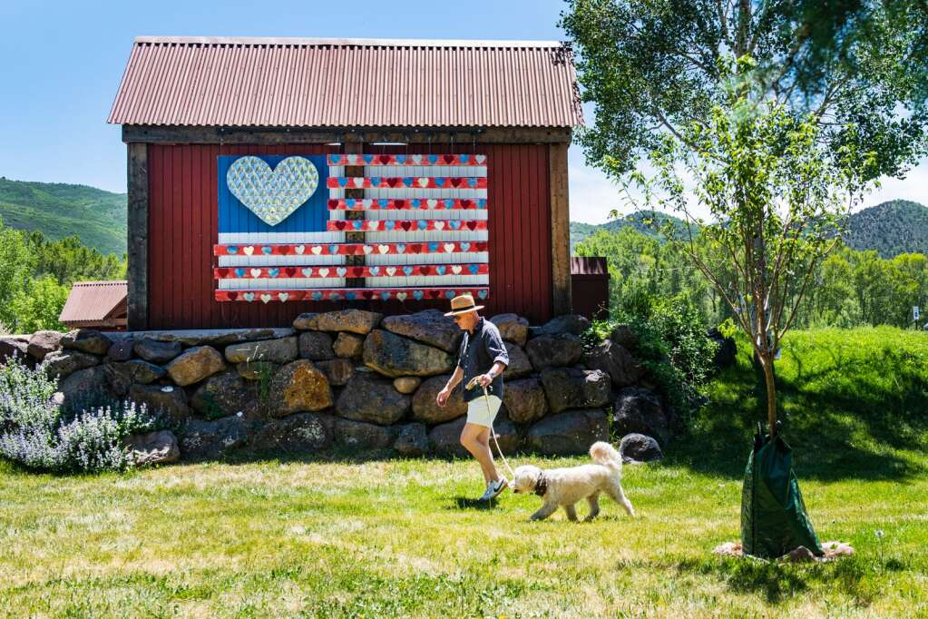 A man and his dog pass by John Przonek's 3D mural of an American Flag displayed on the back of the RFTA bus stop at Lions Park behind the Basalt Town Hall on Wednesday, June 9, 2021. (Kelsey Brunner/The Aspen Times)