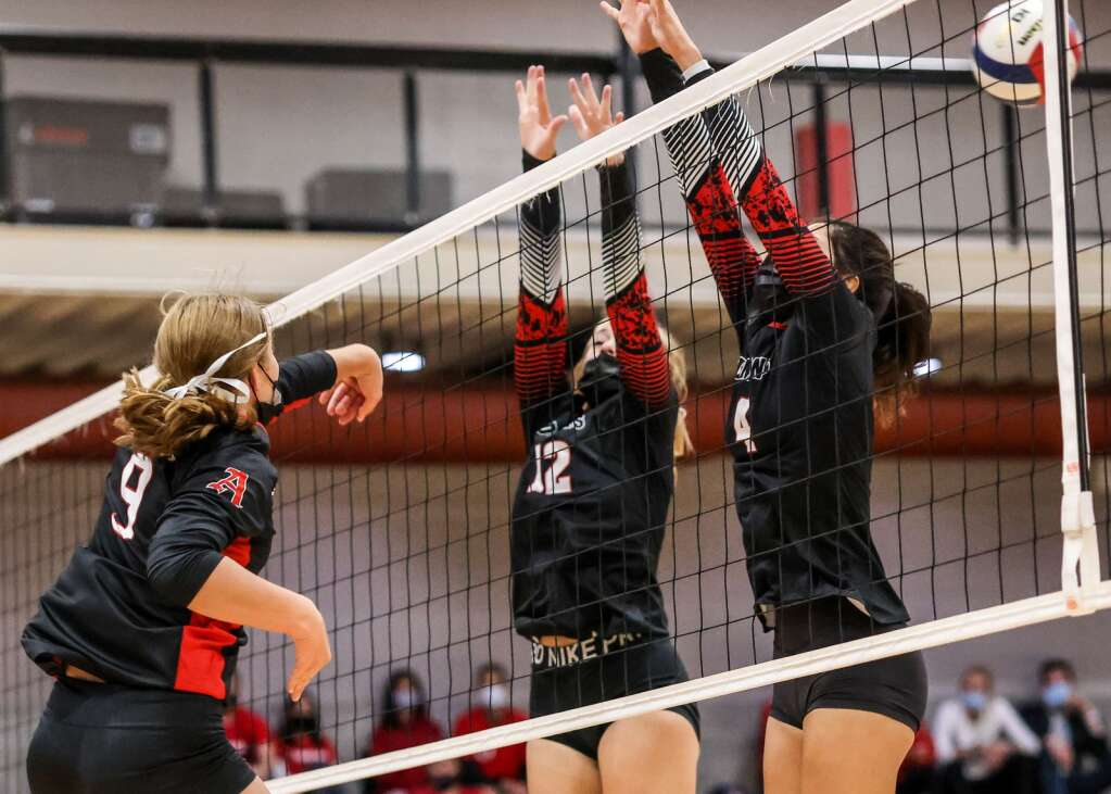 Aspen High School's Maddie Lee, left, delivers the ball past a pair of Glenwood Springs volleyball players on Thursday, Aug. 19, 2021, inside the AHS gymnasium. The Skiers won, 3-2. | Photo by Austin Colbert/The Aspen Times