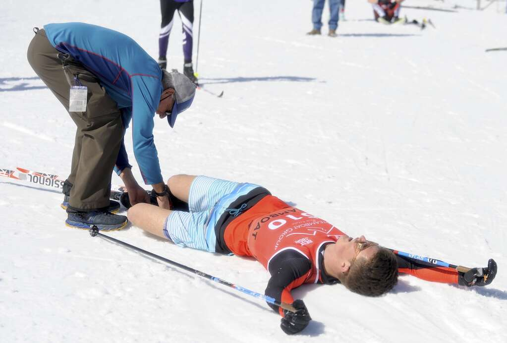 Steamboat Springs head Alpine Coach Mike Farny takes a timing chip off of Alden Wade's ankle after the classic race at the state skimeister championships at Howelsen Hill on Tuesday, March 9.