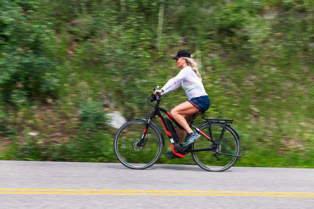 A woman rides an e-bike to the Maroon Bells on Maroon Creek Road in Aspen on Thursday, July 22, 2021. (Kelsey Brunner/The Aspen Times)