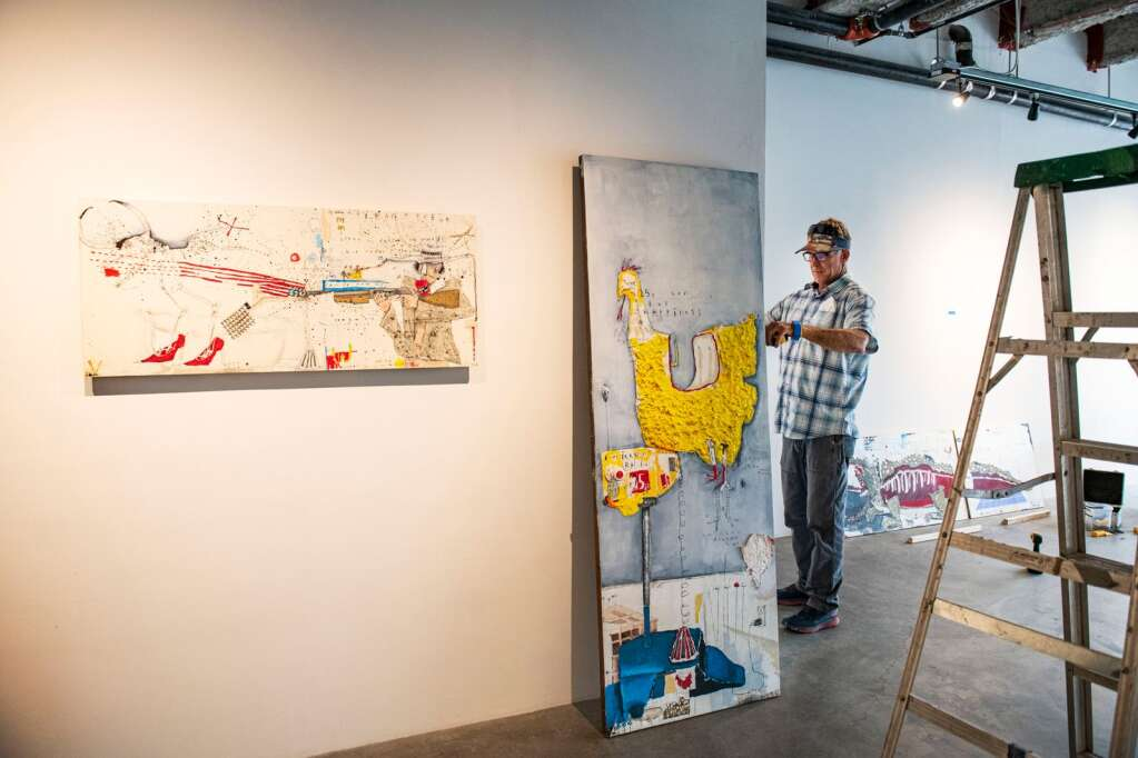Wade Livingston prepares to hang one of his Axel Livingston's pieces in the Gonzo Gallery for his son's first show in the space in Aspen on Tuesday, April 27, 2021. (Kelsey Brunner/The Aspen Times)