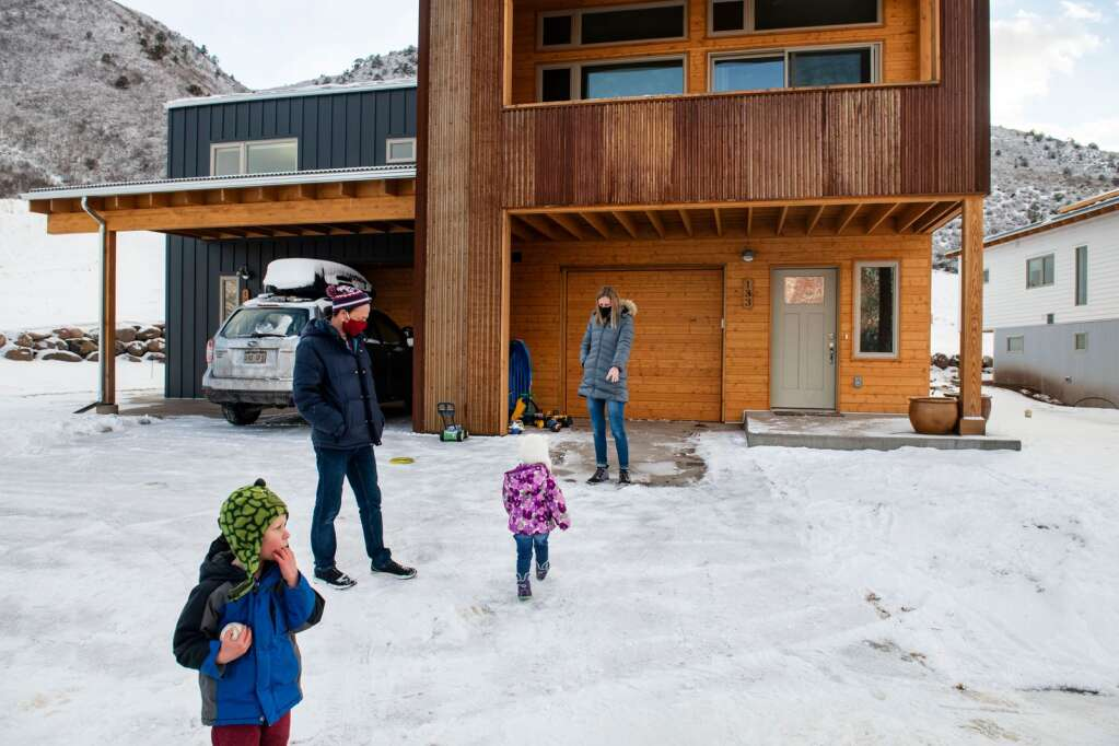 Arlo Duncan, 4, left, Jeremy Duncan, Willa Duncan, 2, and Lyssa Duncan play in the snow outside of their home in Basalt Vista behind Basalt High School on Friday, Feb. 5, 2021. The family of four moved into their home in September. (Kelsey Brunner/The Aspen Times)