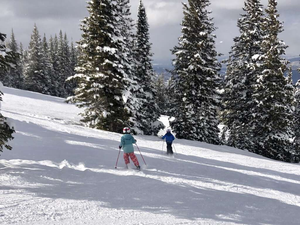 Sisters Emily and Siri Bassion ski into the Powerline Glades at Snowmass on day 113 of the season on March 17, 2021. The sisters are aiming for a perfect season this year after earning their 100-day pin. | Kaya Williams/The Aspen Times