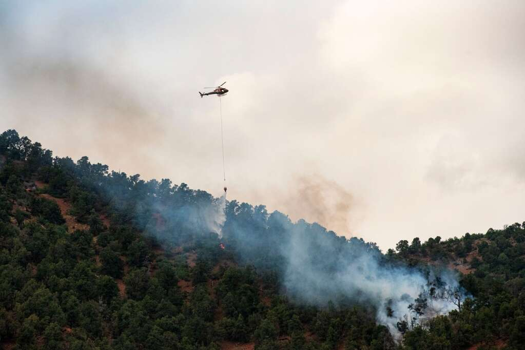 A helicopter drops water on a flame attempting to contain the fire before it spreads further along the ridge above Lower River Road in Old Snowmass on Friday, June 18, 2021. (Kelsey Brunner/The Aspen Times)