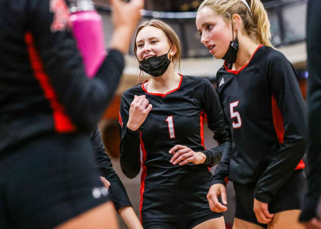 Aspen High School's Sadie Bayko, center, and Avery Leonard, right, listen in during a timeout as the AHS volleyball team hosts Glenwood Springs on Thursday, Aug. 19, 2021, inside the AHS gymnasium. The Skiers won, 3-2. Photo by Austin Colbert/The Aspen Times.