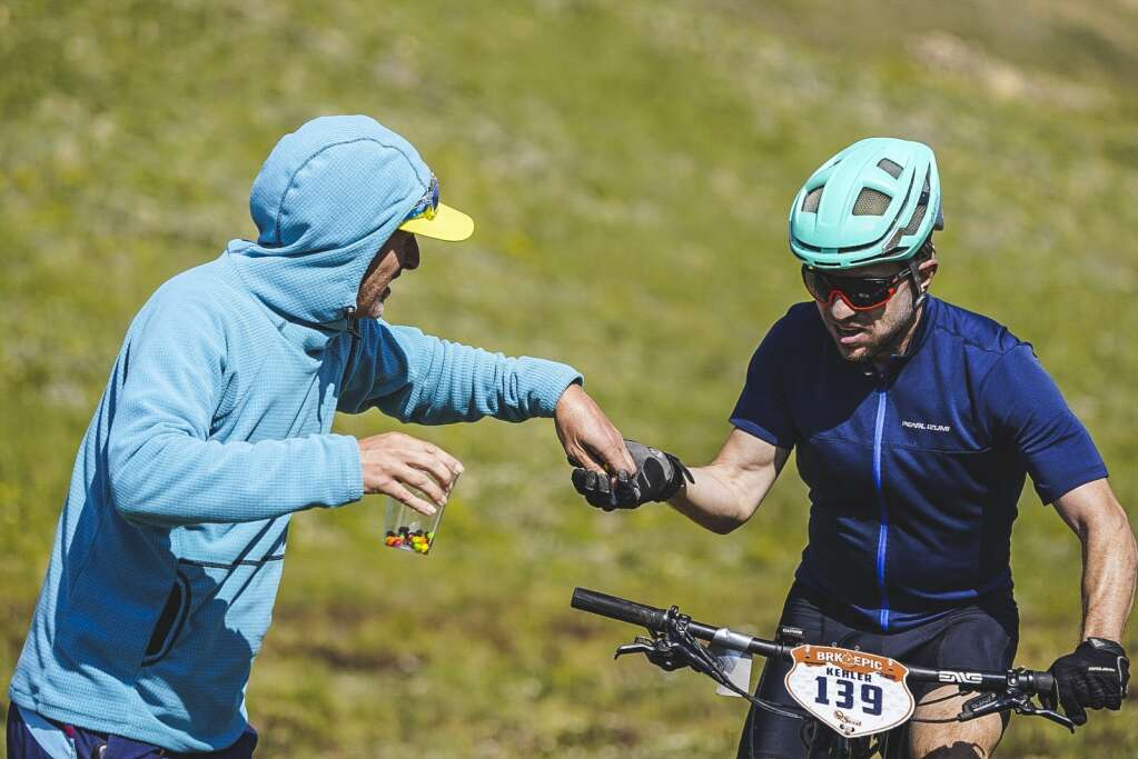 Stephen Kehler prepares to take a handful of Skittles from race supporters at the top of French Pass during Tuesday's third stage of the six-day Breck Epic mountain bike race. | Photo by Devon Balet / Breck Epic