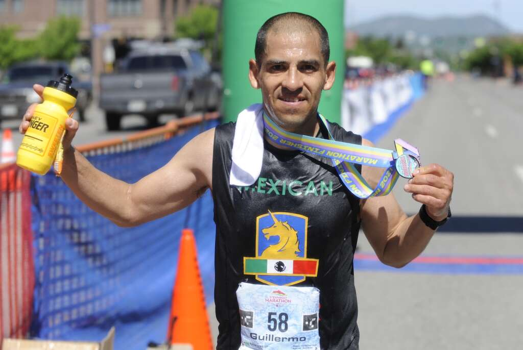 Guillermo Ceja holds up his finish line swag after completing the Steamboat Marathon on Sunday morning. (Shelby Reardon)