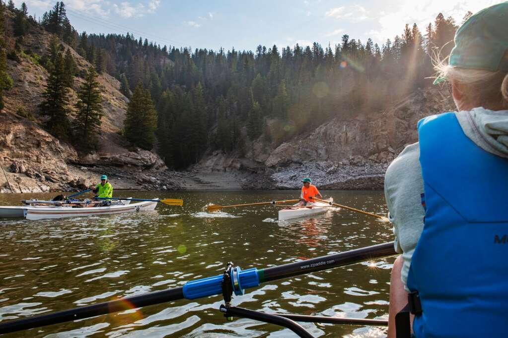 Jack Rafferty, left, Steve Prudden and Laura Hanssen chat in a small alcove on Ruedi Reservoir while enjoying the company of their fellow Ruedi Rowers Boat Club members on Tuesday, July 13, 2021. Rafferty said he usually could spot an eagle in this area of the reservoir. (Kelsey Brunner/The Aspen Times)