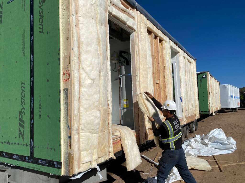 A construction workers unpacks a module delivered to the site of Burlingame Ranch phase three.