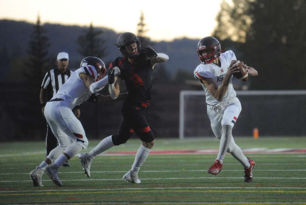 An Aspen player runs the football during the homecoming football game at Steamboat Springs on Friday night. | Shelby Reardon/Steamboat Pilot & Today