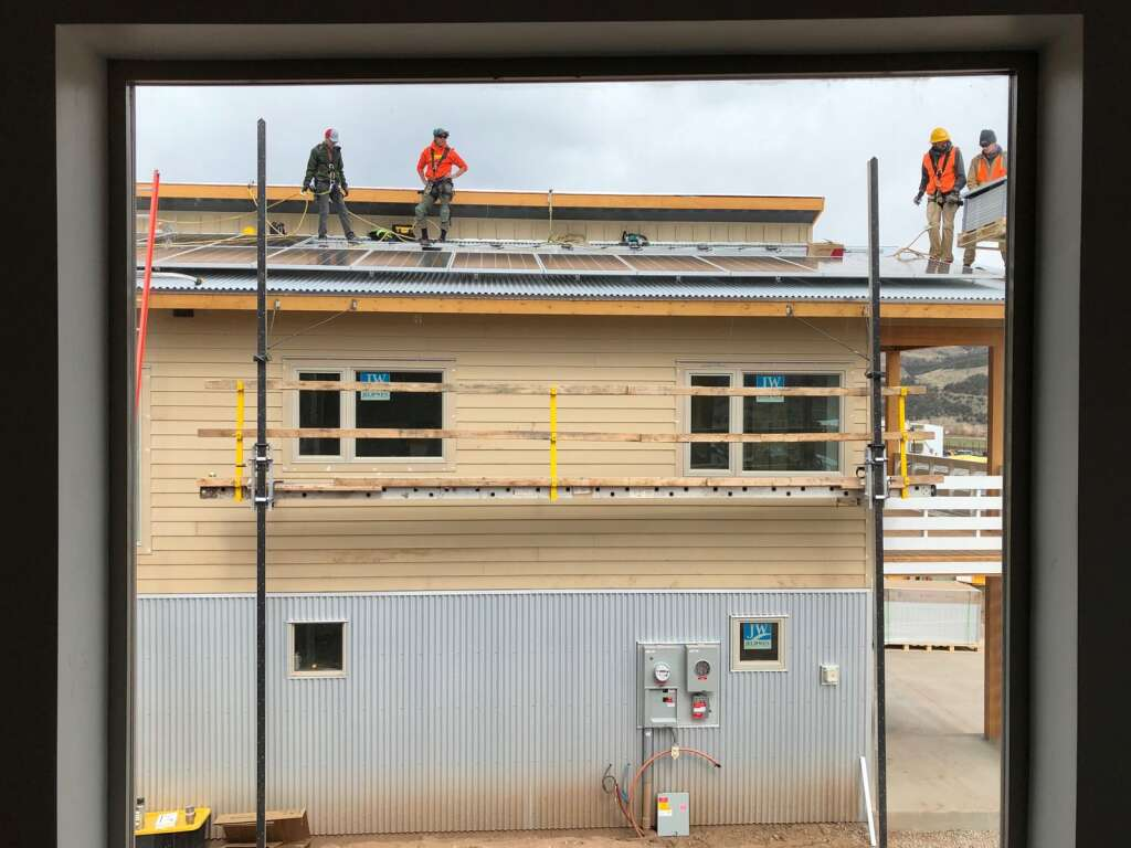 Workers from Sunsense Solar install panels on a unit at Basalt Vista on Thursday, April 22. The view is from the window of a neighboring unit. | Scott Condon/The Aspen Times