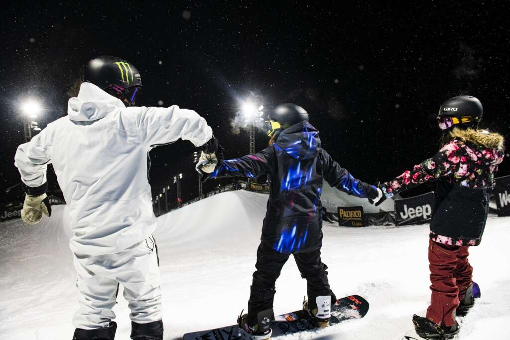 Japanese snowboarders hold hands and do the wave at the top of the superpipe at Buttermilk during the first night of practice for the 2021 X Games in Aspen on Tuesday, Jan. 26, 2021. (Kelsey Brunner/The Aspen Times)
