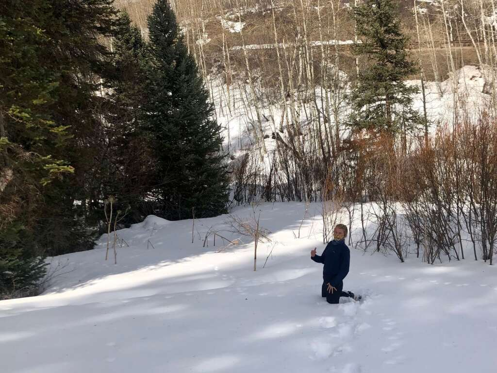 Aspen Center for Environmental Studies naturalist Nicole Goodman demonstrates snow depth near the Nature Trail in Snowmass Village during a guided trek on March 9, 2021. | Kaya Williams/The Snowmass Sun