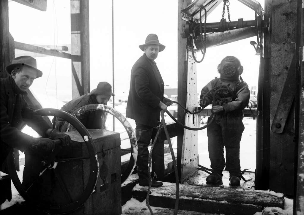 A deep sea diver (Fred Johnson) is about to descend underground in the Smuggler Mine to renew the packing in a pump that had been drowned out. The man helping him is George Peterson, both of New York. The stalled pump was about 65 feet under water. The other two men identified in the paper as Jesse Yates, far left, and Joe Hull on the other side of the crank wheel. 1910 - Published on the front page of the November 30, 1910 Aspen Democrat-Times paper. | Aspen Historical Society
