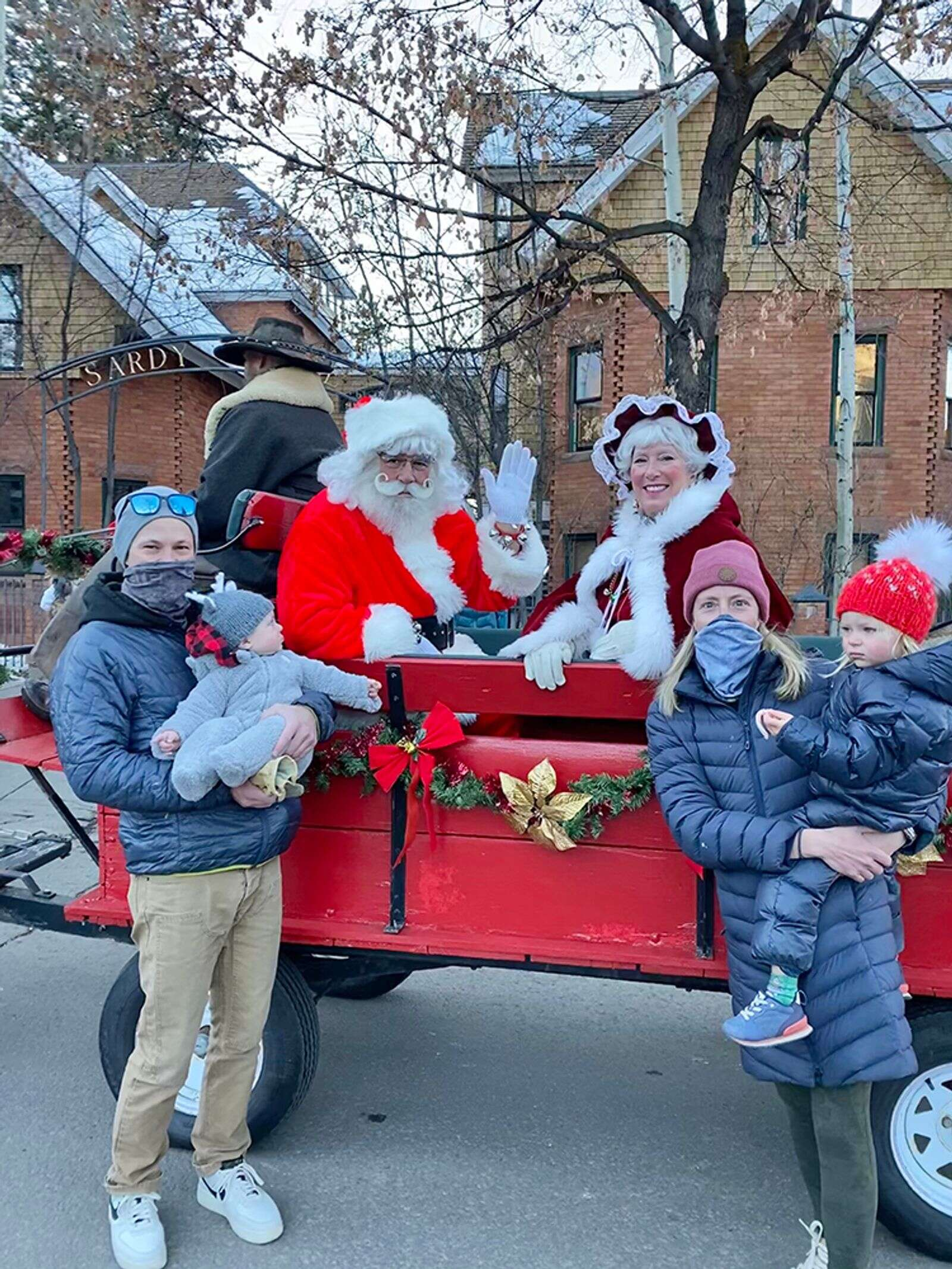 Chace and Chelsey Dillon with their children, Charlie and Stella, greet Santa and Mrs. Claus for their carriage ride around town.