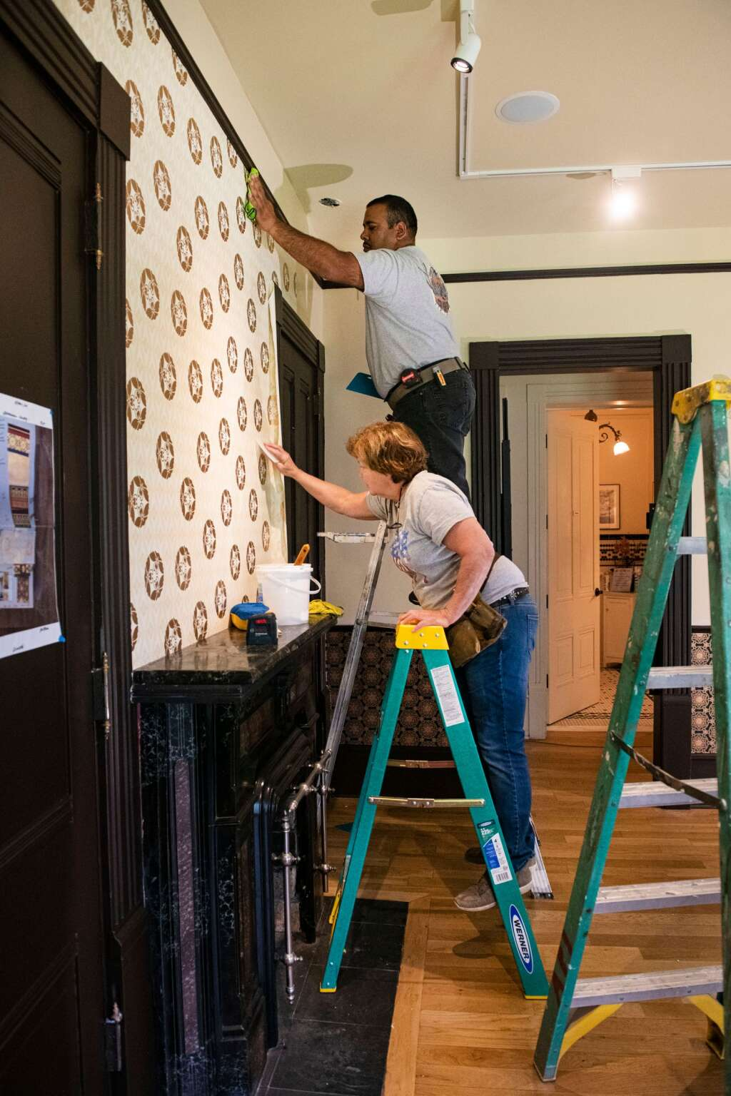 Dizan Quezada and Janie Zelenka apply wallpaper to the walls of a room in the Aspen Historical Society's victorian Wheeler-Stallard Museum on W. Bleeker St. in Aspen on Wednesday, May 12, 2021. (Kelsey Brunner/The Aspen Times)
