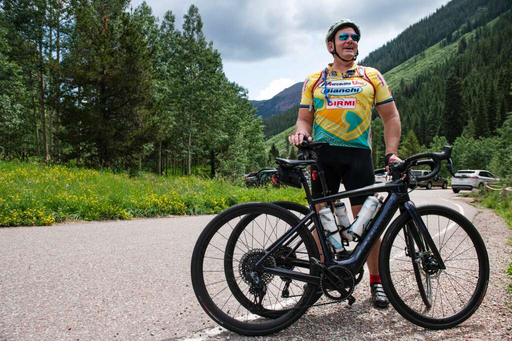 Curt Schreur stands in the parking lot at the top of Maroon Creek Road to visit Maroon Bells holding e-bikes in Aspen on Thursday, July 22, 2021. (Kelsey Brunner/The Aspen Times)