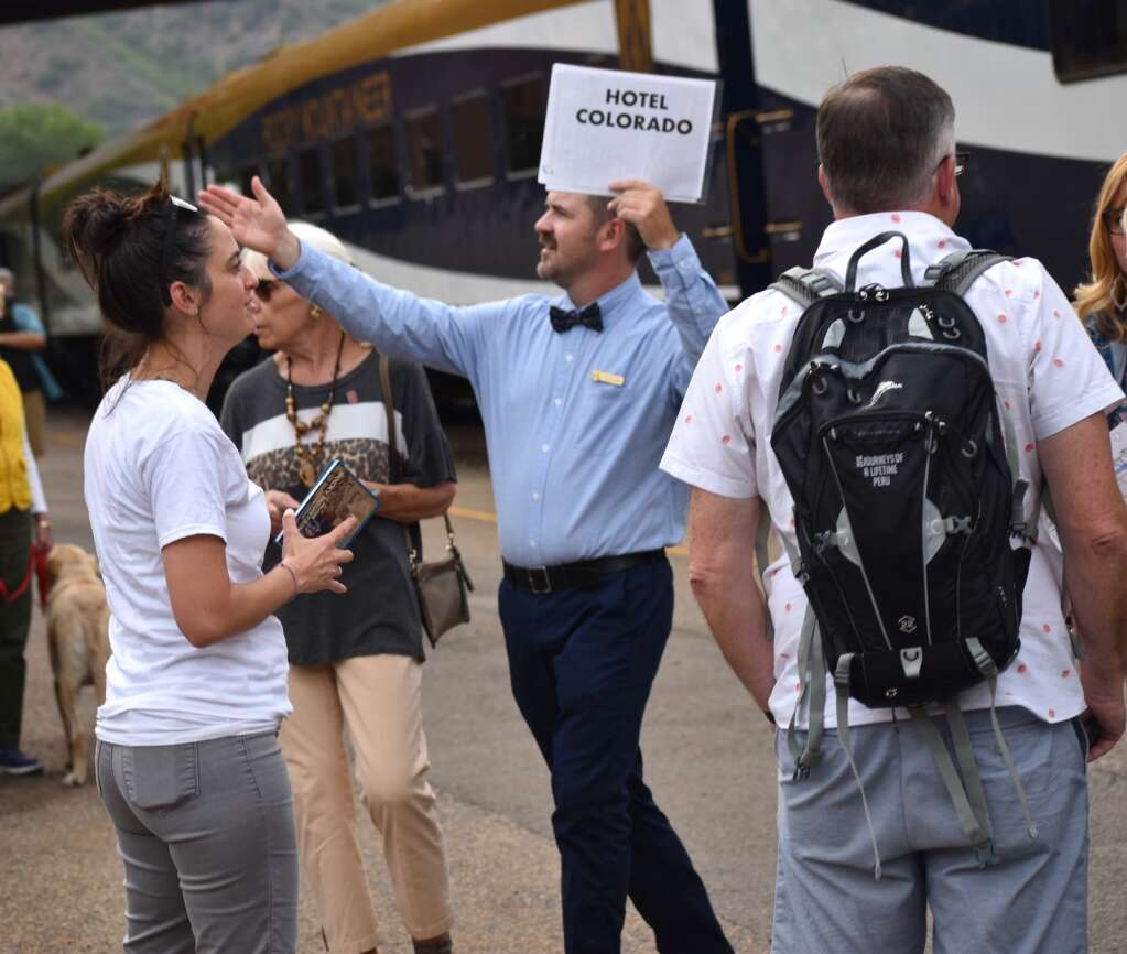 An assistant points Rocky Mountaineer train passengers to their hotel destination outside the Glenwood Springs Train Station Sunday.