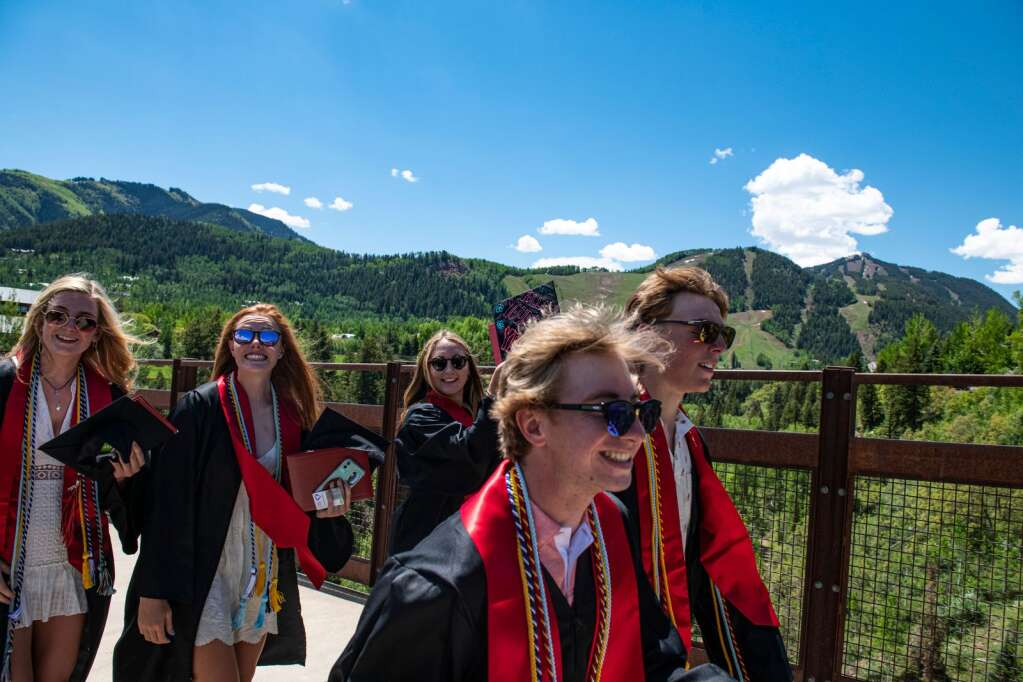 Aspen High School graduates walk across the bridge to Tiehack after their commencement ceremony at the school on Saturday, June 5, 2021. (Kelsey Brunner/The Aspen Times)